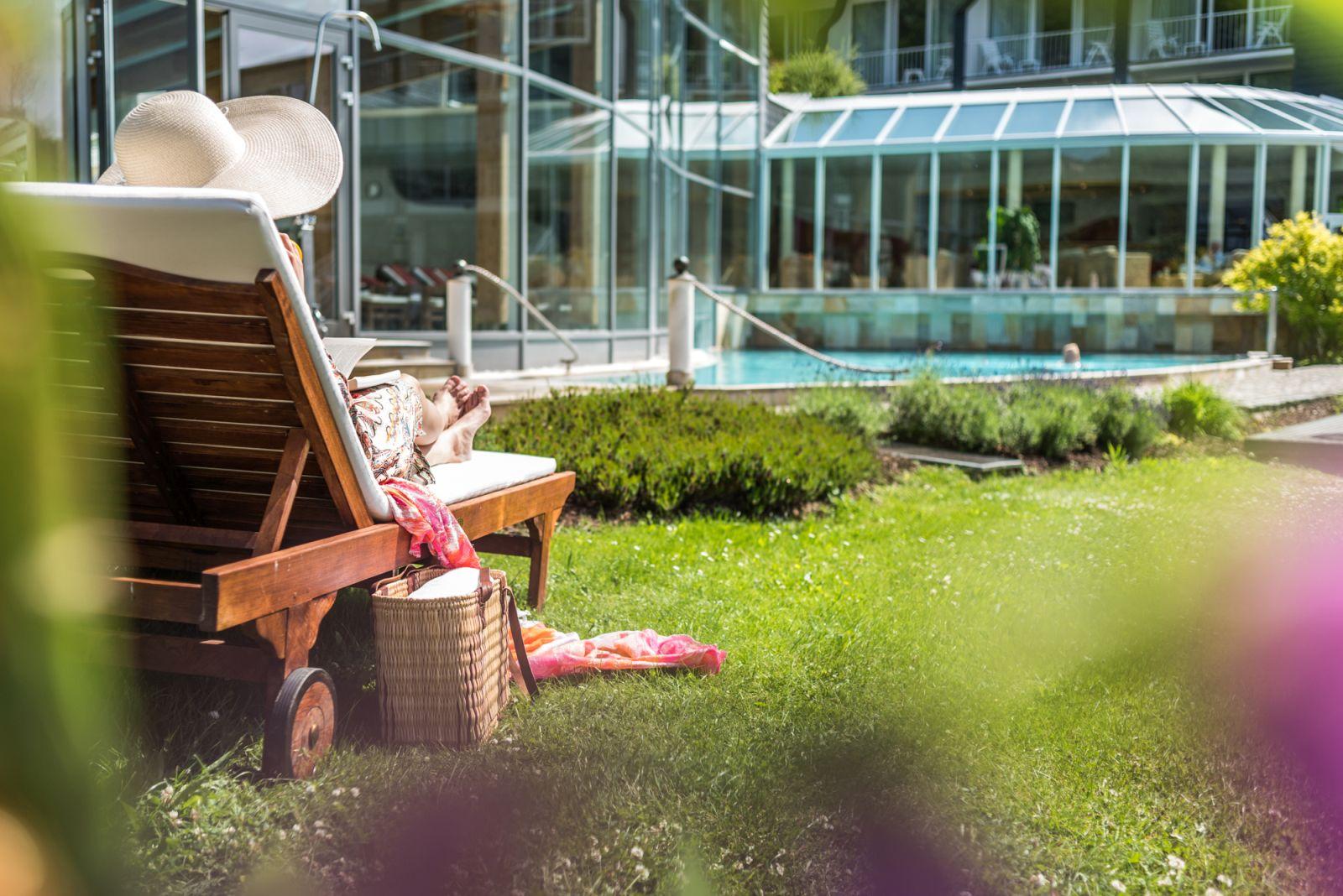 Frau im Liegestuhl im Garten mit Blick auf den Außenpool im Hotel Deimann