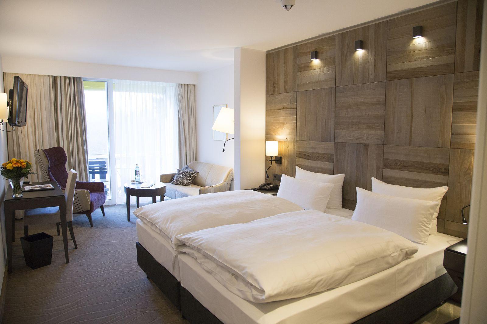 Doppelzimmer mit Holzvertäfelter Bettrückwand und Sitzecke im Jagdhaus Wiese