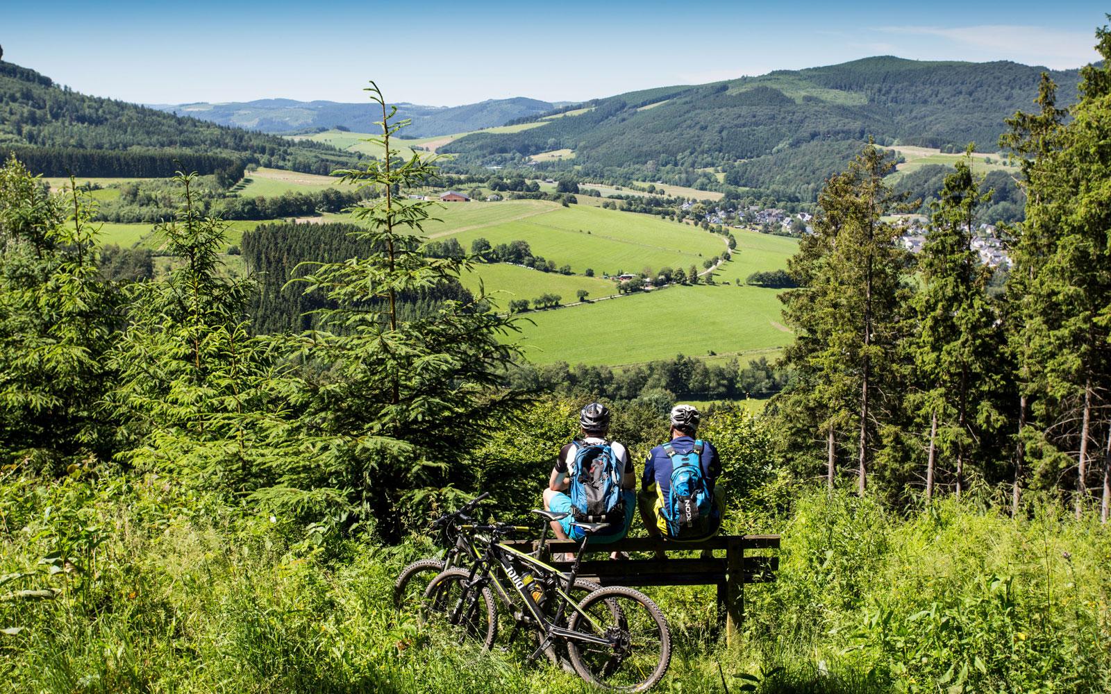 Zwei Radfahrer auf einer Bank mit Aussicht ins Tal