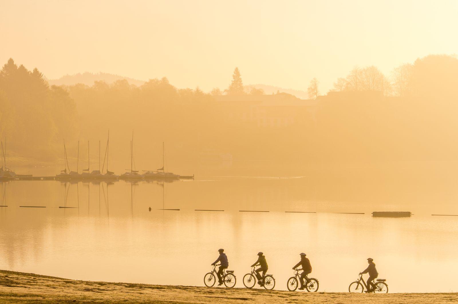 4 Radfahrer am Strand eines Sees in der Abendsonne