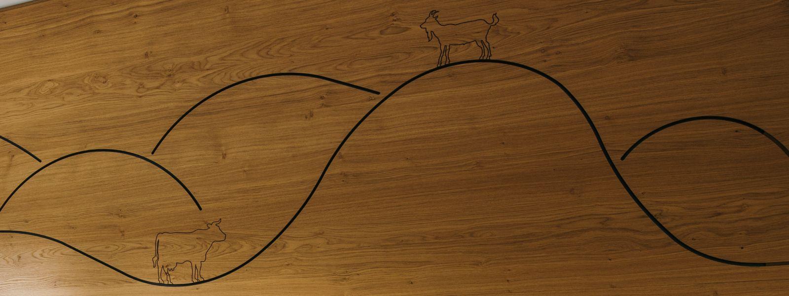 Schöne Holzschnitzerei mit Hügeln, einer Kuh und einer Ziege