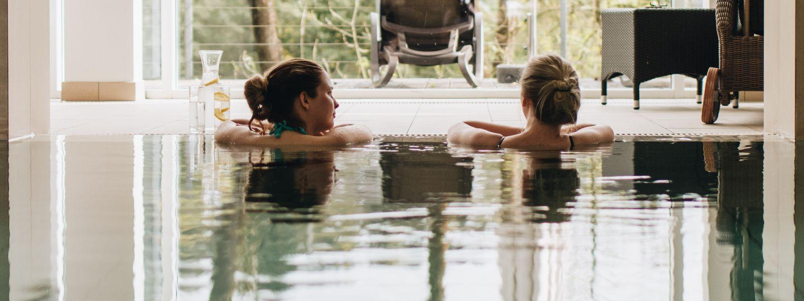 Zwei Freundinnen beim Gespräch am Poolrand