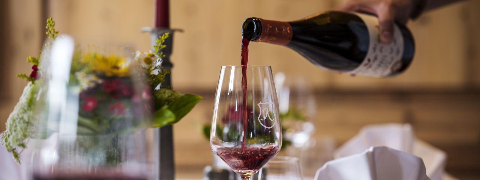 Ein Rotwein wird in eine Glas geschenkt für Romantik pur