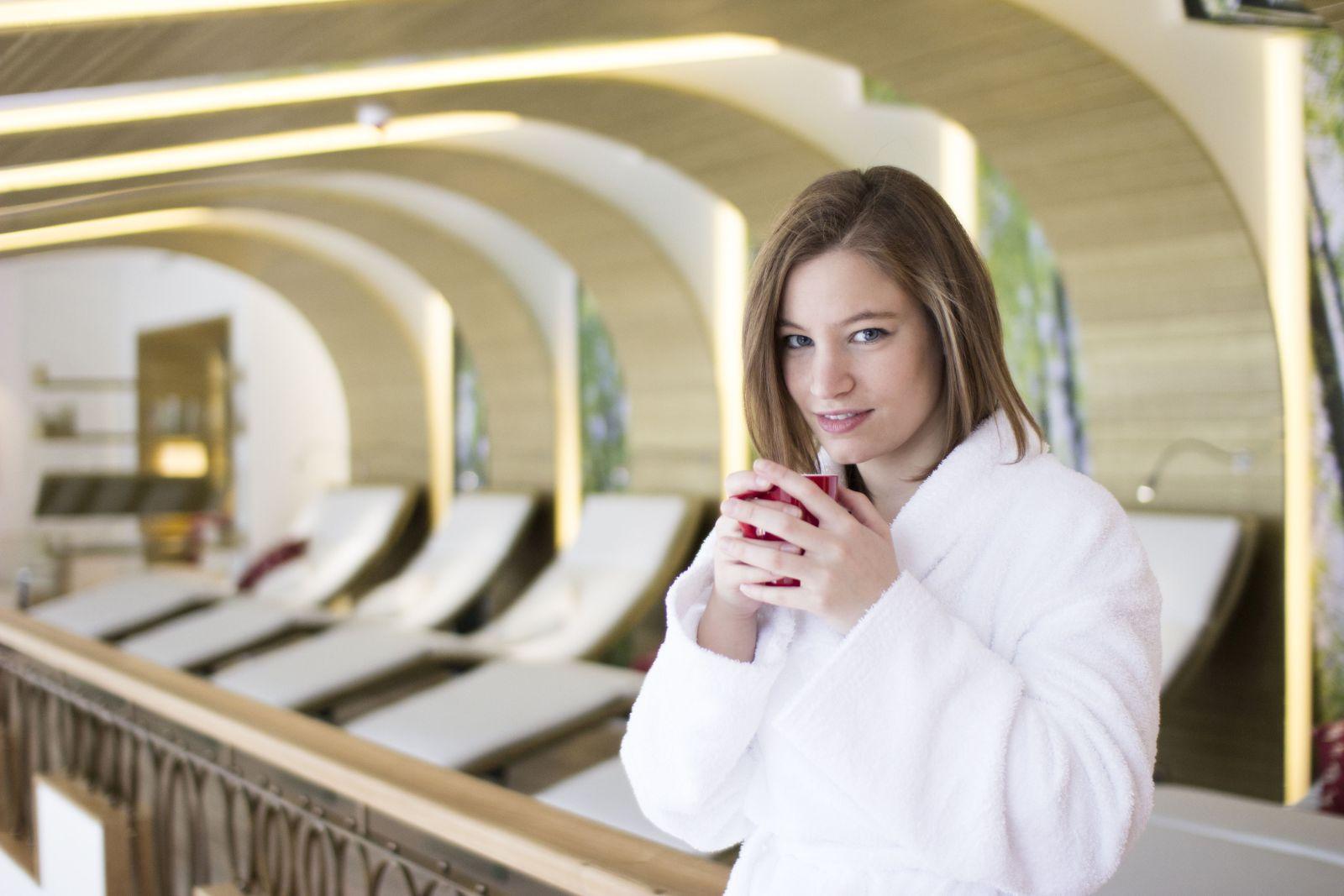 Junge Frau mit Bademantel und Tasse Tee im Ruheraum vom Jagdhaus Wiese